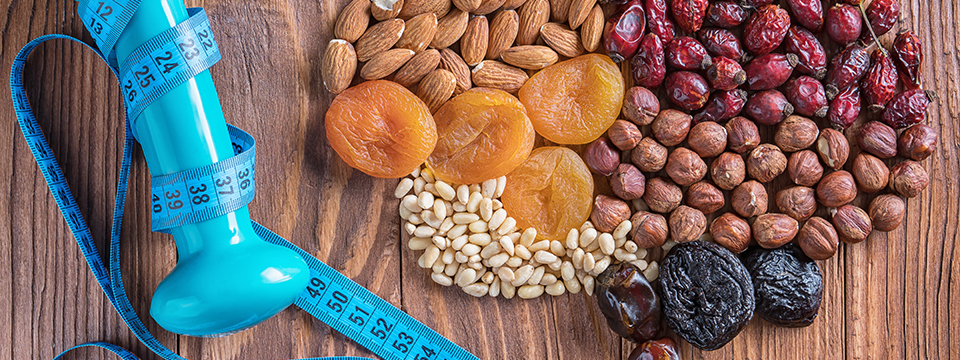 A number of healthy ingredients are arranged in the shape of a human brain including dried oranges, cranberries, almonds dates and other nuts and seeds.