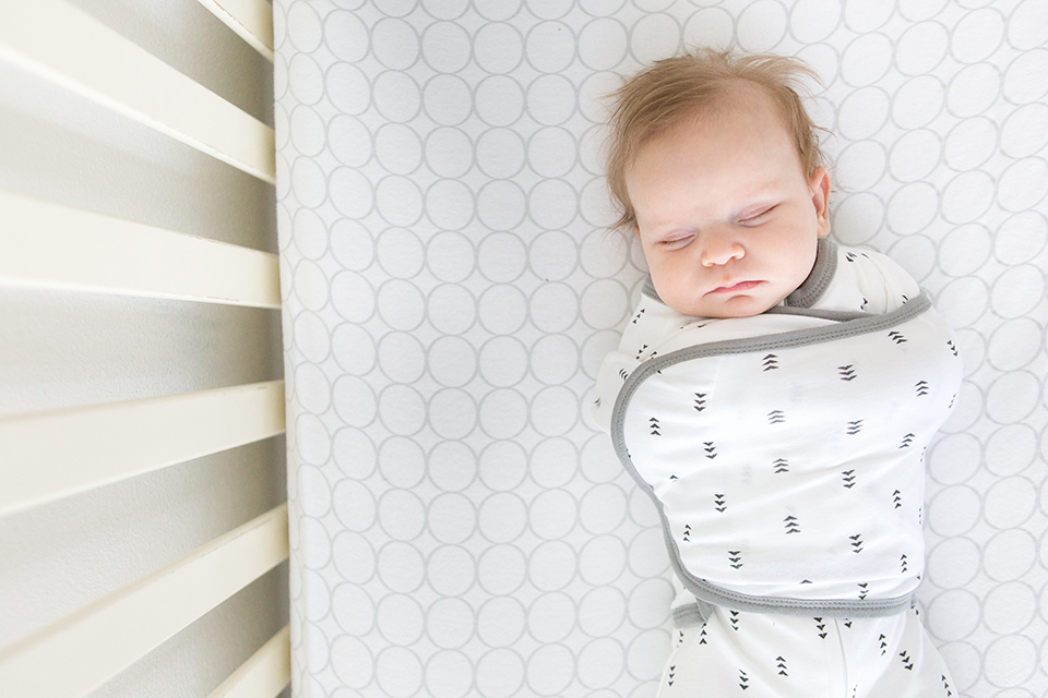 A newborn baby sleeps contentedly. Safe sleep environment for baby in cotton omni swaddle sack.